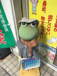 薬局の外にある冬服を着たかえるの像