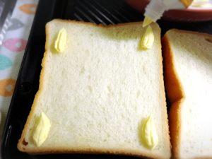 食パンにチューブのバターを付ける様子