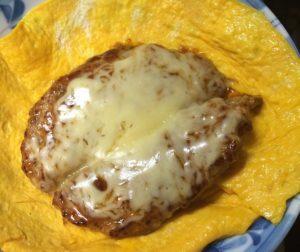 チーズのせハンバーグを卵の薄焼きにのせた様子