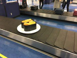 大分空港の荷物ベルトコンベアの上の寿司の置き物