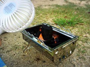 ロゴスのグリルの炭火に手持ち扇風機で風を当てる様子