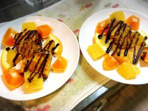 チョコレートソース掛けカステラフレンチトーストと柑橘系フルーツを盛った皿2枚