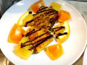 チョコレートソース掛けカステラフレンチトーストと柑橘系フルーツを盛った皿