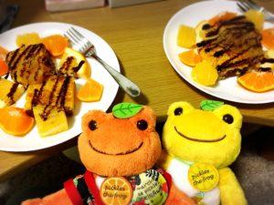 チョコレートソース掛けカステラフレンチトーストと柑橘系フルーツを盛った皿2枚とかえるのぬいぐるみたち