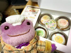PRIROLLのかえるのピクルスのカップケーキとノベルティの缶バッジとかえるのぬいぐるみ
